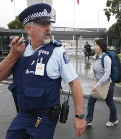 A New Zealand police officer escorts a relative of missing Japanese students to a bus at Christchurch airport on Friday. Tuesday's earthquake has left more than 100 people dead.
