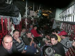 Romanian evacuees from Lybia sit inside a Hercules C-130 military airplane on their way to Romania on Friday.