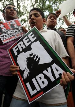 A Libyan living in Malaysia holds a placard during a protest against Libyan leader Moammar Gadhafi outside the Libyan Embassy in Kuala Lumpur on Friday.
