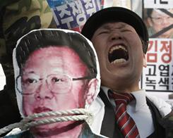 A South Korean Vietnam War veteran shouts slogan behind a portrait of North Korean leader Kim Jong Il during a rally against him Friday in Seoul.