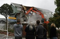 Bryony, Brent and Shannon Smith look on as their house is demolished Saturday in Christchurch, New Zealand.