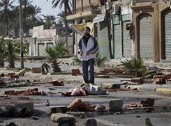 A man walks on Saturday through roadblocks made by residents in the Tajoura district of eastern Tripoli, Libya. Residents blocked streets after pro-regime militiamen opened fire on Friday.