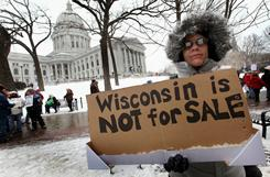Jeannine Ramsey joins thousands of other demonstrators marching around the Capitol building protesting the proposed budget repair bill Saturday in Madison, Wis.