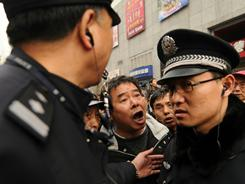 In Shanghai, protesters shout at police. China's one-party system does not permit anti-government protests, so gatherings are monitored.