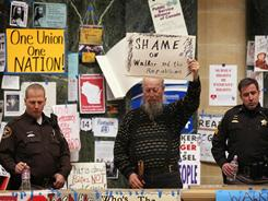 William Thibodeau, center, protests Sunday amid a police presence in the rotunda of the Wisconsin Capitol in Madison.