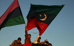 Anti-government protesters wave their old national flag during Monday's rally in the eastern Libyan city of Benghazi.