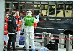 Police officers and ambulance staff stand in front of a U.S. military bus after a shooting March 2 at the airport in Frankfurt, Germany.