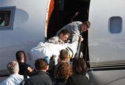 Rep. Gabrielle Giffords is carried onto an airplane in Tucson as she is transferred to a rehab center in Houston on Jan. 21.