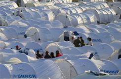 Refugees who fled from Libya, stand among tents at a refugee camp on Wednesday, near the Tunisian city of Ben Guerdane.