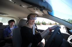 Chattahoochee student Yvonne Ploder wears goggles that simulate impairment as Davis Nix rides along.