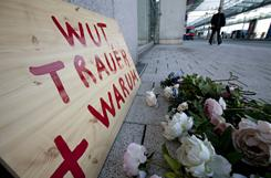 """Plastic flowers and a wooden plate reading """"Anger  Sorrow  Why"""" are laid down Thursday at the airport in Frankfurt, Germany, where a lone gunman killed two U.S. airmen."""