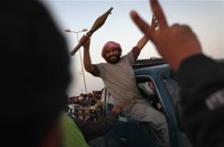 A rebel fighter greets comrades while heading toward the front line Thursday in Ajdabiya, Libya.