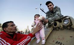 A man hands his child to a soldier to take a picture of him on top of a personnel carrier during a demonstration Friday in Cairo.