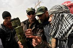 A Libyan defected soldier, second from left, explains how to use a rocket launcher to rebels Friday on the outskirts of Ras Lanuf before heading into the town to battle Moammer Gadhafi loyalists.