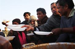 Bangladeshi migrant workers who recently crossed into Tunisia from Libya wait to receive food in a United Nations displacement camp Friday in Ras Ajdir.