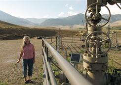 Environmentalist Deb Thomas stands next to the Crosby 25-3 gas well, which blew out in 2006 when it was being drilled in the Line Creek Valley, about 40 miles east of Yellowstone National Park.
