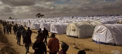 Men who worked in Libya but recently fled the unrest walk on Saturday in a refugee camp in Ras Ajdir, Tunisia.