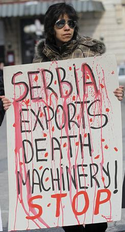 "A member of anti-war organization ""Women in Black"", holds a banner reading ""Serbia exports death machinery! Stop."" during the organization's anti-war protest Feb. 28 in Belgrade, Serbia."