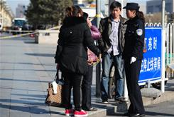 A police officer questions a woman Sunday near Tiananmen Square in Beijing amid heightened security.