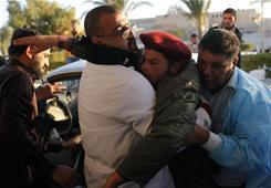 A Libyan rebel, wounded during the fight against pro-Gadhafi forces, is carried to a hospital in the oil town of Ras Lanouf.