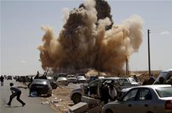 Anti-Gadhafi fighters run for cover as a bomb explodes Monday near a checkpoint outside of Ras Lanouf. 