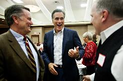 Mitt Romney, center, jokes with Michael Sununu, right, of Newfields, N.H., and Bayard Kennett, of North Conway, N.H., while making his way around the ballroom, table-to-table, to greet guests at the Attitash Grand Summit Hotel in Bartlett, N.H., on Saturday.