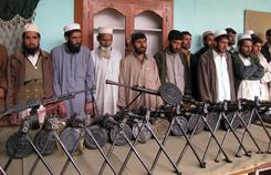 Some militants who have surrendered, along with machine guns seized, are presented to the media last February near the Pakistani-Afghan border.