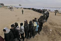 Migrants from Bangladesh wait in line for food at a Tunisia-Libyan border refugee camp on Tuesday.