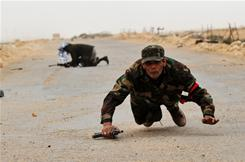 Libyan rebel fighters run for cover Tuesday as shells explode around them near Bin Jawwad.