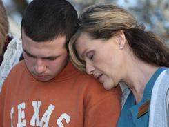 Suzanne Randle puts her head on the shoulder of her stepson Dylan Randle, who was attacked at his high school in New Albany, Miss.