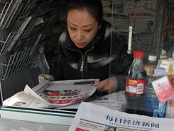A newspaper vendor in Beijing reads articles Wednesday about the expected appointment of U.S. Commerce Secretary Gary Locke as the next U.S. Ambassador to China.