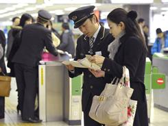 Staff help stranded bullet train passengers after service is suspended following a 7.2 earthquake hits northern Japan.