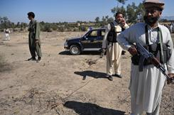 Pakistani anti-Taliban militia stand guard at a suicide blast site in the village of Adezai, near Peshawar on Wednesday.