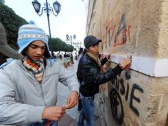 Students clean graffiti from a wall Saturday where protesters had gathered in Tunis.