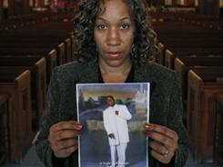 Pam Bosley stands inside the St. Sabina Catholic Church with a photograph of her son, Terrell, who was gunned down in 2006. Bosley said no one is in custody in her son's death, but whoever killed him does not deserve to live.