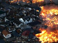 Houses burn after being hit by a tsunami at Natori city in Miyagi prefecture, northern Japan, on Friday.