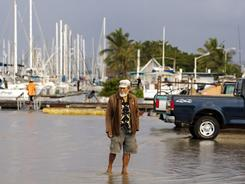 A man walks in a flooded parking lot in Honolulu after a tsunami hit Hawaii on Friday.