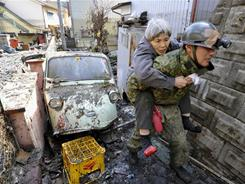 A stranded elderly woman is carried on the back of a Japanese soldier after being rescued from a residence at Kesennuma, northeastern Japan, on Saturday.
