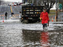After passing underneath the closed Saw Mill Parkway, Colette Storti, of Tarrytown, N.Y., wades through flood waters along Route 119 on her way to work Friday in Elmsford, N.Y.