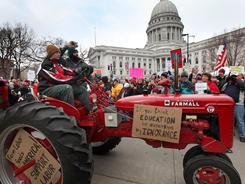 A farmer drives his tractor past the Wisconsin state Capitol during a rally on Saturday.