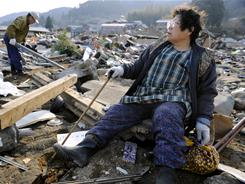 A woman sits among ruins Sunday in the coastal town of Ofunato, Japan, where a powerful earthquake hit the country's east coast on Friday.
