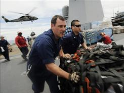 U.S. Navy personnel prepare Friday to send humanitarian aid to Japan.