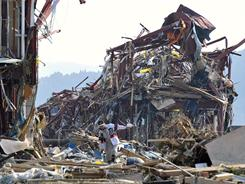 A man walks amid the rubble in northern Japan on Sunday, two days after a powerful earthquake and tsunami hit the country's coast.
