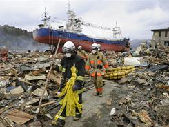 Firefighters make their way through the rubble left behind by Friday's massive quake and tsunami in northeastern Japan.