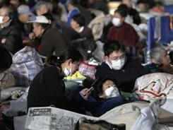 A woman attempts to use her cellphone at a shelter in the Miyagi Prefecture town of Watari. The official death toll hit 2,414, but more than 10,000 were still missing.