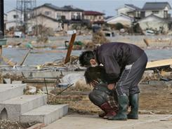 A man comforts a woman as she cries Monday in front of her damaged home in the town of Watari in Miyagi Prefecture.