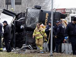 Emergency workers investigate the scene of a bus crash on Interstate 95 in New York on Saturday in which 15 people were killed.