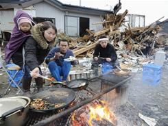 Tsunami survivors cook and eat in front of their damaged house Tuesday in Ishinomaki in Miyagi Prefecture.