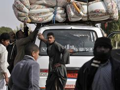 Evacuees from Libya pile up belongings atop their car as they cross the Egyptian border into the town of Sallum on Wednesday.