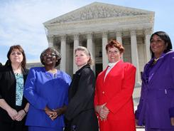 Five of the six named plaintiffs in the Wal-Mart v. Dukes case, from left, Stephanie Odle, Betty Dukes, Christine Kwapnoski, Deborah Gunter and Edith Arana, pose for photographers in front of the Supreme Court  on Tuesday.